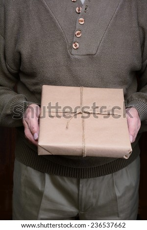 Closeup of a man holding a parcel in front of his torso.  - stock photo