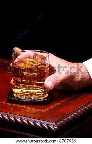 Closeup of a man holding on to his glass of whiskey on the rocks and a cigar on an elegant wood table. Vertical format with a black background. - stock photo