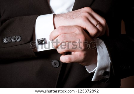 Closeup of a man in black suit correcting a sleeve - stock photo