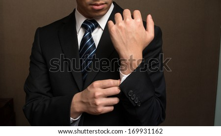 Closeup of a man in black suit correcting a sleeve. - stock photo