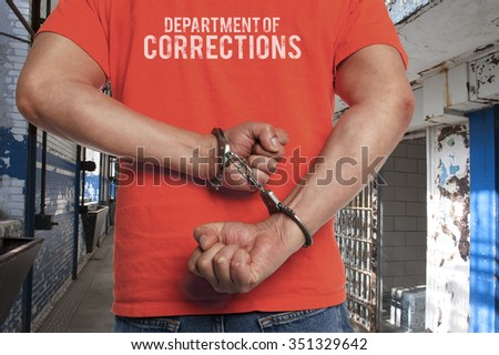 Closeup of a man in prison struggling against the handcuffs binding his arms behind his back - stock photo