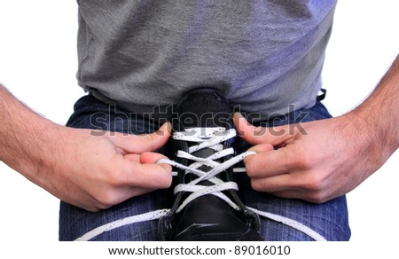 closeup of a man lacing a kid ice skate - stock photo