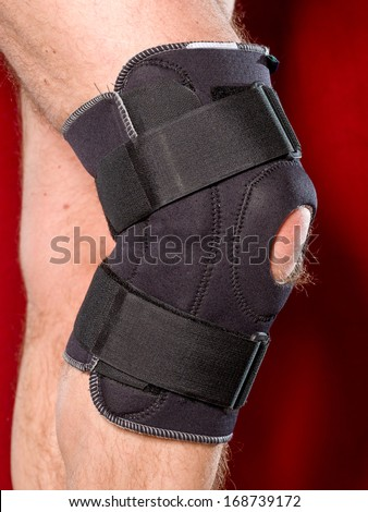 Closeup of a man legs with one knee in a protective knee brace - stock photo