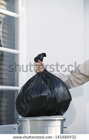 Closeup of a man putting garbage bag into trash can - stock photo