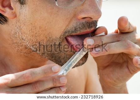 Closeup of a man rolling hashish joint. - stock photo