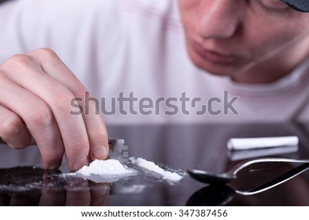 Closeup of a man's hand cutting cocaine on a glass table with razor blade - stock photo