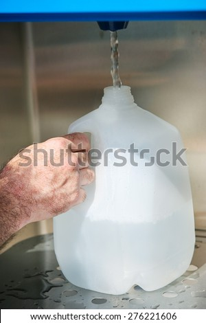 Closeup of a man's hand filling a gallon jug from a water machine.   - stock photo
