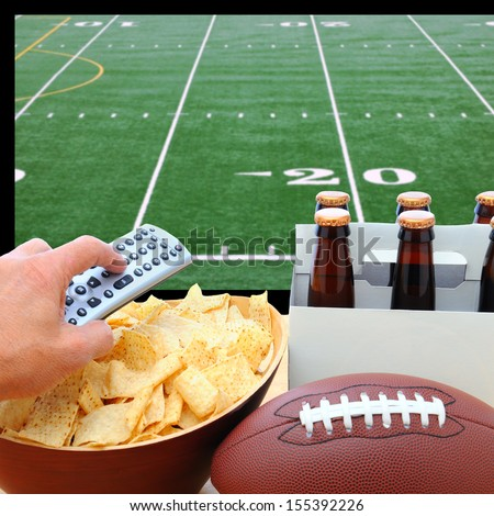 Closeup of a man's hand holding a TV remote with a bowl of chips and a six pack of beer with a football field on the television screen in the background. Square Format. - stock photo