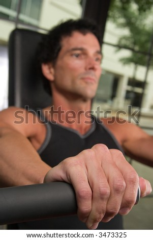 Closeup of a man's hand on an arm exercise machine in a fitness center.  The hand is in clear focus with shallow depth of field causing the man's face to be out of focus. - stock photo