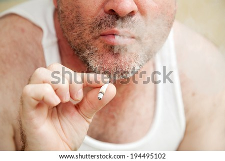 Closeup of a man smoking a joint and blowing smoke.