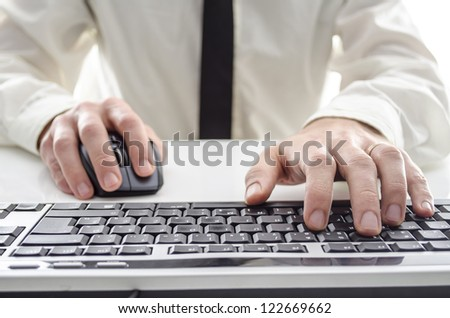 Closeup of a man using computer. His shirt and tie in background. - stock photo