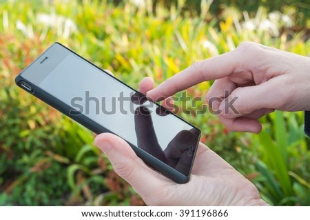 Closeup of a man using mobile smart phone outdoor. Garden background.