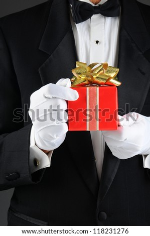 Closeup of a man wearing a tuxedo holding a christmas present in front of his body. Vertical format, Man is unrecognizable. - stock photo