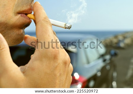 closeup of a man with a burning cigarette in his mouth while is waiting besides a car parked next to a no traffic road - stock photo