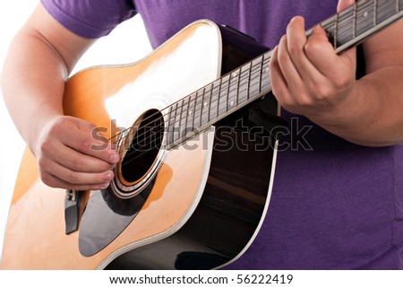 Closeup of a mans hands strumming and electric acoustic guitar isolated over a white background. - stock photo