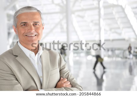 Closeup of a mature businessman with his arms folded in an airport concourse. The man is smiling at the camera with blurred passengers in the background. - stock photo