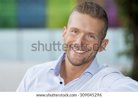 Closeup Of A Mature Man Smiling At The Camera. He is outside of the office - stock photo