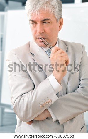 Closeup of a mature smiling business man standing in a light at his office near white board. - stock photo