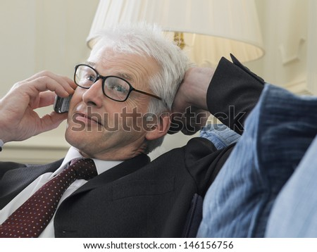 Closeup of a middle aged businessman using mobile phone on sofa - stock photo