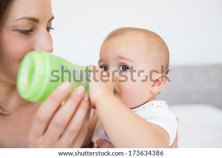 Closeup of a mother feeding baby with milk bottle at home - stock photo