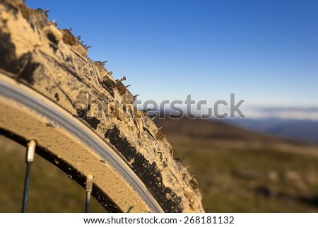 Closeup of a muddy bicycle wheel and tire in countryside. - stock photo