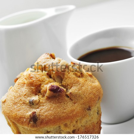 closeup of a muffin in a plate and a cup of coffee on a set table - stock photo
