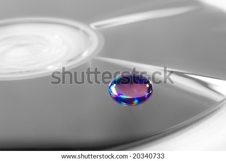 Closeup of a multicolored beautiful drop of water on a B&W surface - stock photo