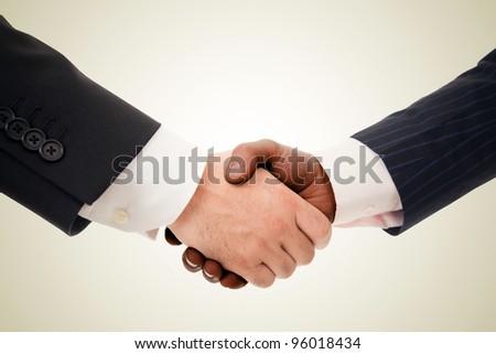 Closeup of a multiracial handshake between two business men - stock photo