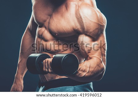 Closeup of a muscular young man lifting dumbbells weights on dar - stock photo