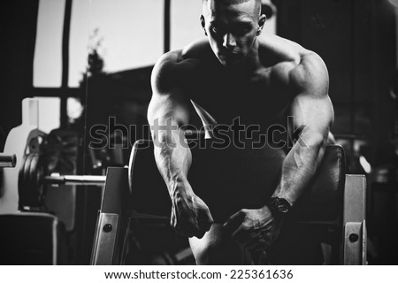 Closeup of a muscular young man lifting weights. Fine art. B&W - stock photo