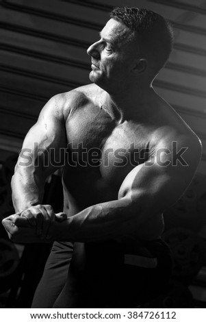 Closeup of a muscular young man lifting weights on dark background.