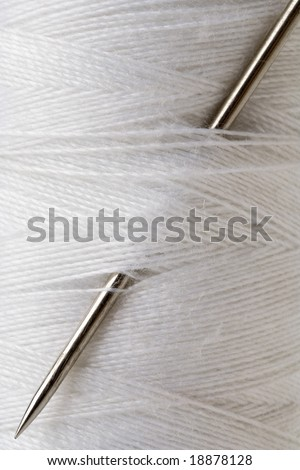 closeup of a needle stuck in a spool of white thread