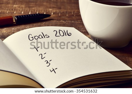 closeup of a notebook with a blank list of goals for 2016 and a cup of coffee on a rustic wooden table - stock photo