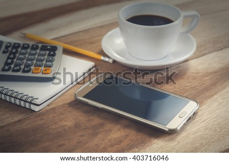 closeup of a notebook with text written in it and smart phone on table