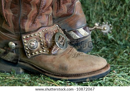 closeup of a pair of cowboy boots with spurs on alfalfa - stock photo