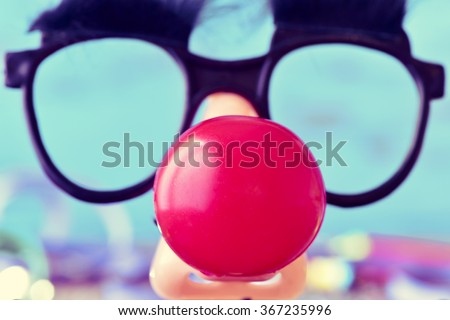 closeup of a pair of fake black glasses with eyebrows and a red clown nose forming the face of a man, against a blue background - stock photo