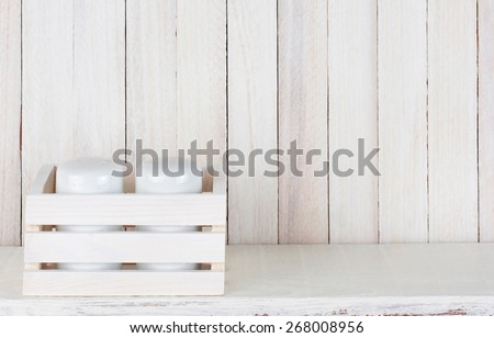 Closeup of a pair of salt and pepper shakers in a small wood box on a white wood rustic kitchen shelf. Horizontal format with copy space. - stock photo