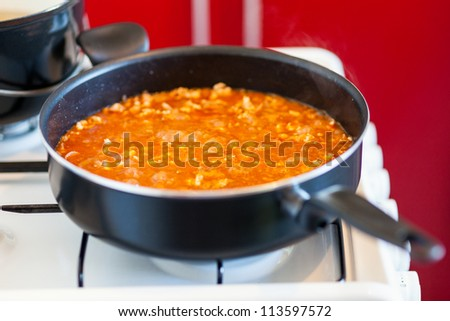 Closeup of a pan sauce on a stove while preparing food - stock photo