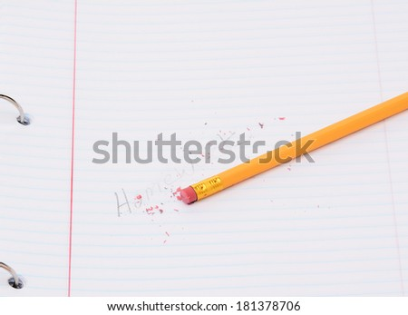 Closeup of a pencil on a notebook page with the word homework partially erased. Back to school concept.  - stock photo