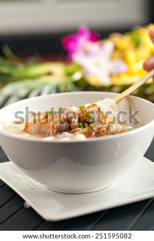 Closeup of a person eating Thai style crispy pork rice noodle soup from a bowl with chopsticks. Pineapple fried rice in the background. - stock photo