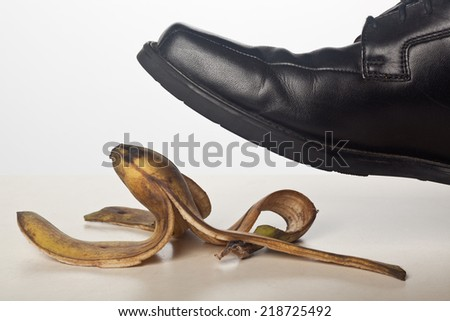 Closeup of a person's foot stepping on a banana peel  - stock photo
