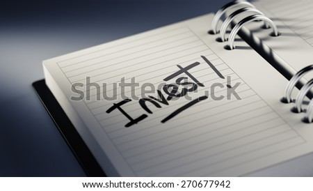 Closeup of a personal agenda setting an important date representing a time schedule. The words Invest written on a white notebook to remind you an important appointment.