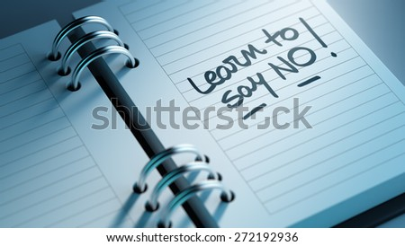 Closeup of a personal agenda setting an important date representing a time schedule. The words Learn to say no written on a white notebook to remind you an important appointment. - stock photo