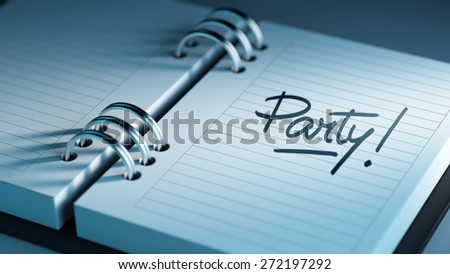 Closeup of a personal agenda setting an important date representing a time schedule. The words Party written on a white notebook to remind you an important appointment.