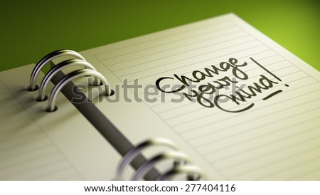 Closeup of a personal agenda setting an important date representing a time schedule. The words Change your Mind written on a white notebook to remind you an important appointment. - stock photo