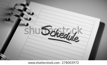 Closeup of a personal agenda setting an important date representing a time schedule. The words Schedule written on a white notebook to remind you an important appointment.