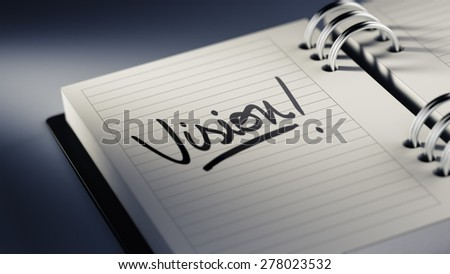 Closeup of a personal agenda setting an important date representing a time schedule. The words Vision written on a white notebook to remind you an important appointment.