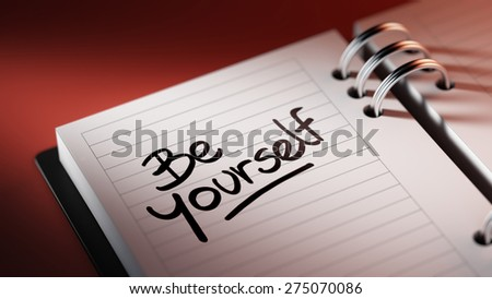 Closeup of a personal agenda setting an important date representing a time schedule. The words be yourself written on a white notebook to remind you an important appointment.
