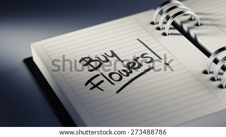 Closeup of a personal agenda setting an important date representing a time schedule. The words Buy Flowers written on a white notebook to remind you an important appointment.