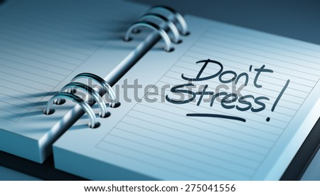 Closeup of a personal agenda setting an important date representing a time schedule. The words Don't Stress written on a white notebook to remind you an important appointment. - stock photo